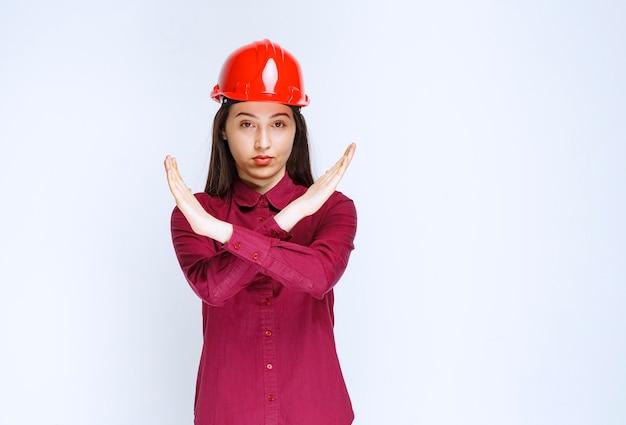 Pewni kobieta architekt w czerwonym kasku twardym pokazując znak stop.