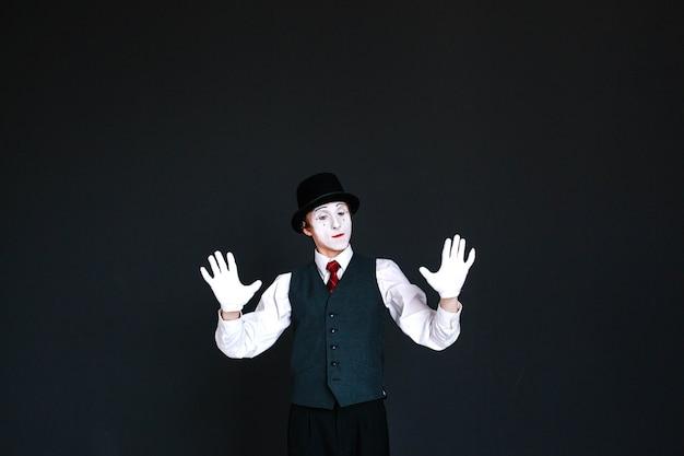 Pewni mime trzyma dłonie w niewidzialnej ścianie