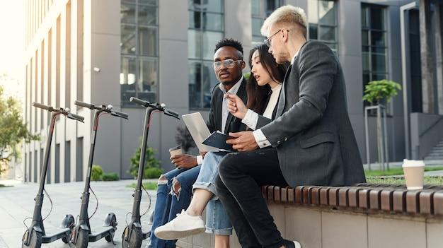 Pewni siebie międzynarodowi współpracownicy siedzą na drewnianej ławce przed biurem i omawiają wyniki