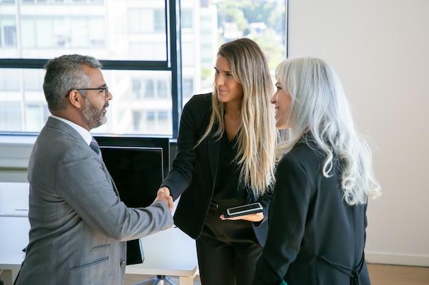 Pewni siebie partnerzy biznesowi spotykają się w biurze, stoją i ściskają ręce, rozmawiają, omawiają współpracę. sredni strzał. koncepcja komunikacji lub partnerstwa