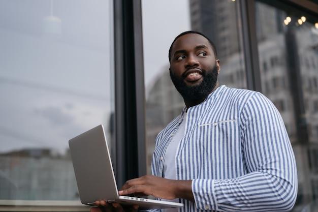 Pewnie afrykański mężczyzna przy użyciu komputera przenośnego, pracujący w trybie online, planowanie uruchomienia. udany biznes