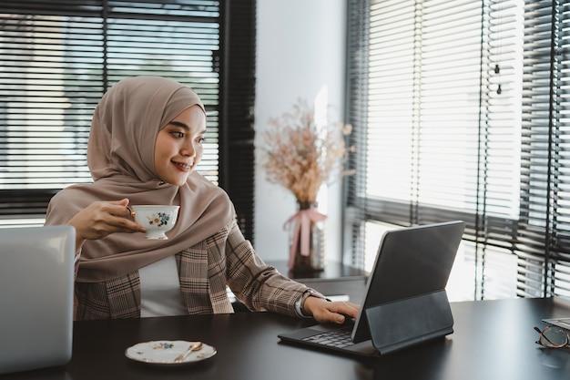 Pewnie azjatycka muzułmańska biznesowa kobieta brązowy hidżab siedzi i pracuje z laptopem w nowoczesnym biurze.