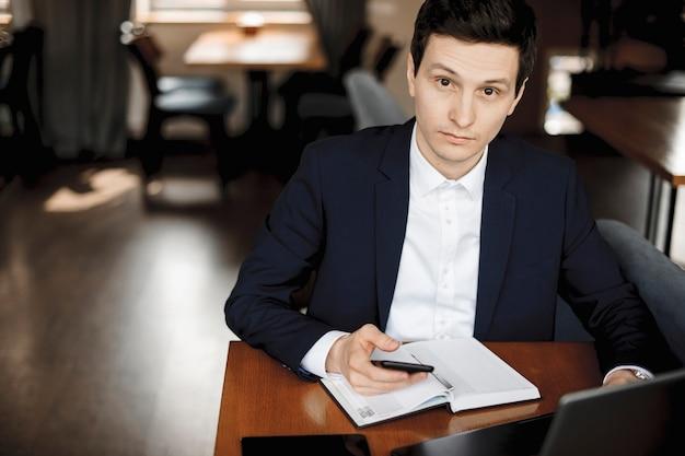 Pewnie biznesmen kaukaski siedzi przy biurku, czekając na obiad, trzymając smartfon