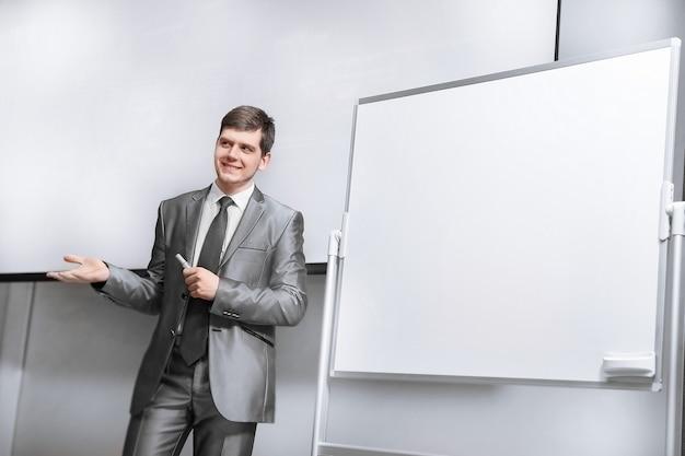 Pewnie biznesmen stojący na scenie w sali konferencyjnej. biznes i edukacja