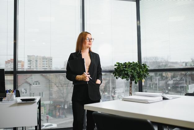 Pewnie biznesowa kobieta stoi w biurze