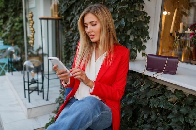 Pewnie blond biznesowa kobieta w czerwonej stylowej kurtce za pomocą telefonu komórkowego i siedząc w miejskiej kawiarni