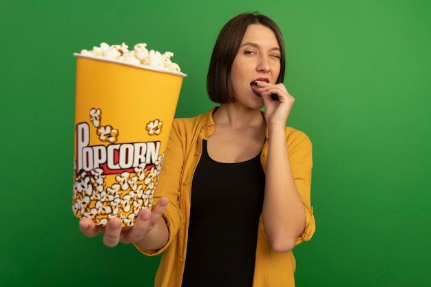 Pewnie całkiem kaukaska kobieta mruga oczami, jedząc i trzymając wiadro popcornu na białym tle