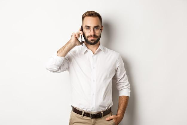 Pewnie człowiek biznesu rozmawia przez telefon, patrząc poważnie, stojąc
