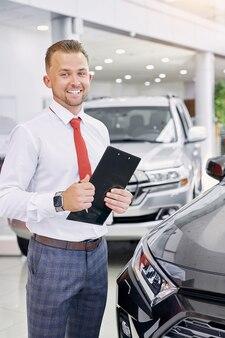 Pewnie kaukaski uśmiechnięty dealer samochodowy w pracy