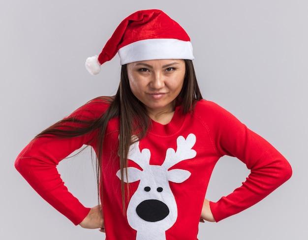 Pewnie młoda azjatycka dziewczyna ubrana w świąteczny kapelusz ze swetrem kładąc ręce na biodrach na białym tle