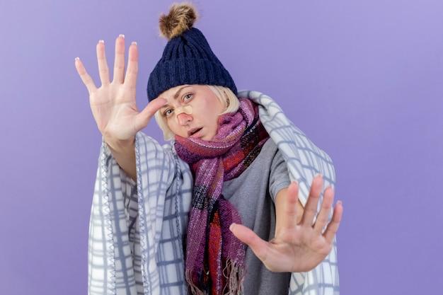 Pewnie młoda blondynka chora słowiańska kobieta z plastrem medycznym na nosie na sobie czapkę zimową i szalik
