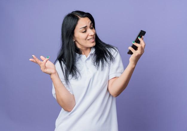 Pewnie młoda brunetka dziewczynka kaukaski trzyma i patrzy na telefon na białym tle na fioletowej ścianie
