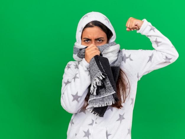 Pewnie młoda chora dziewczyna zakłada kaptur z szalikiem i zakrywa twarz szalikiem i pokazuje silny gest na białym tle na zielonym tle