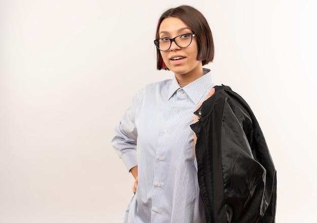 Pewnie młoda dziewczyna call center w okularach, kładąc rękę na talii i trzymając kurtkę na ramieniu na białym tle na biały z miejsca na kopię
