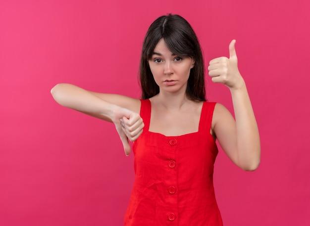 Pewnie młoda dziewczyna kaukaski kciuki w dół i kciuki w górę obiema rękami na na białym tle różowym