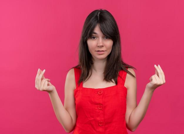 Pewnie młoda dziewczyna kaukaski robi gest pieniędzy obiema rękami i patrząc na kamery na na białym tle różowym tle