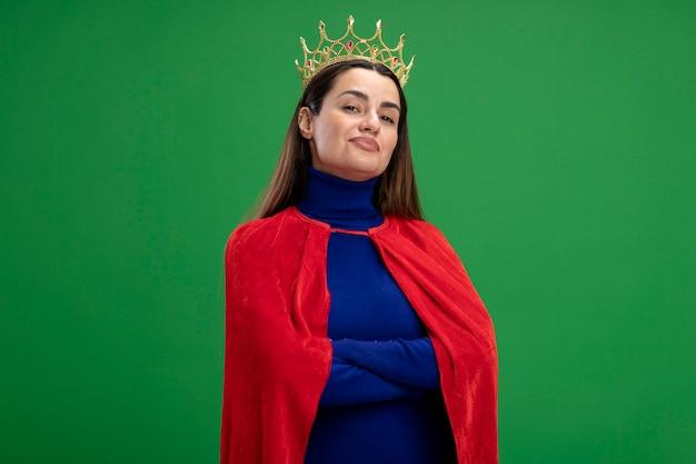 Pewnie młoda dziewczyna superbohatera noszenie korony skrzyżowania rąk na białym tle na zielonym tle