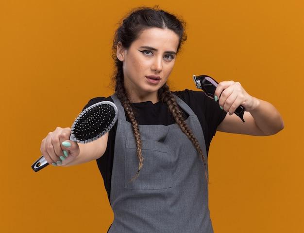 Pewnie młoda kobieta fryzjer w mundurze stojącym w walce pozie trzymając grzebień z maszynką do strzyżenia włosów na białym tle na pomarańczowej ścianie