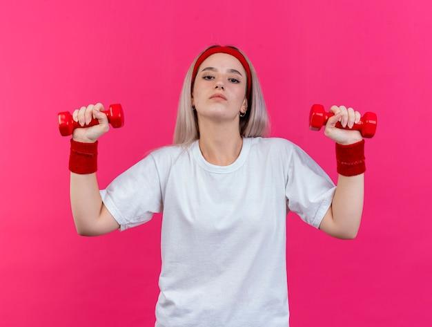 Pewnie młoda kobieta sportowy z szelkami na sobie opaskę i opaski na nadgarstek trzymając hantle na białym tle na różowej ścianie