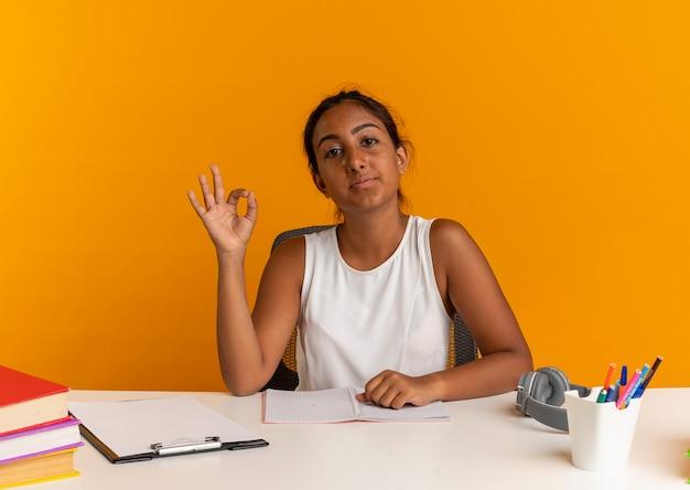 Pewnie młoda uczennica siedzi przy biurku z narzędziami szkolnymi, pokazując gest okey