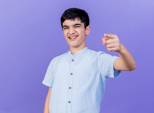 Pewnie młody chłopak kaukaski mrugając, patrząc i wskazując na białym tle na fioletowej ścianie z miejsca na kopię
