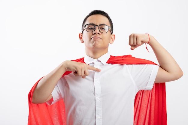 Pewnie młody chłopak superbohatera w czerwonej pelerynie w okularach robi silny gest patrząc na kamery, wskazując na jego mięśnie na białym tle