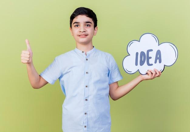 Pewnie młody chłopak trzyma bańkę pomysł, patrząc na przód pokazując kciuk w górę na białym tle na oliwkowej ścianie