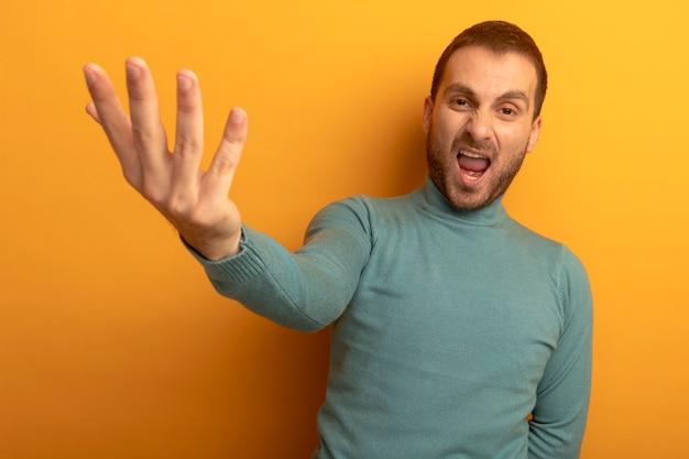 Pewnie młody człowiek kaukaski wyciągając rękę, wyjaśniając coś na białym tle na pomarańczowej ścianie