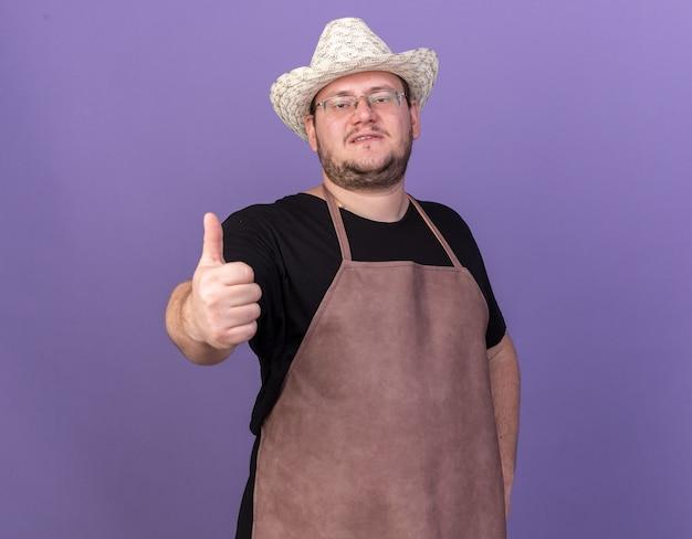 Pewnie młody mężczyzna ogrodnik w kapeluszu ogrodnictwo pokazując kciuk do góry na białym tle na niebieskiej ścianie