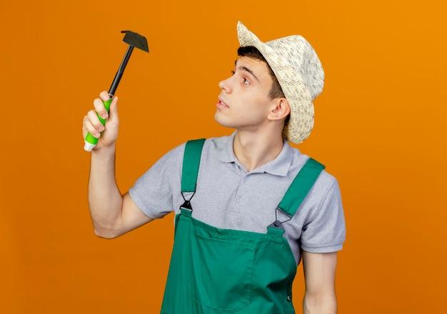 Pewnie młody mężczyzna ogrodnik w kapeluszu ogrodniczym trzyma się i patrzy na motyka grabie
