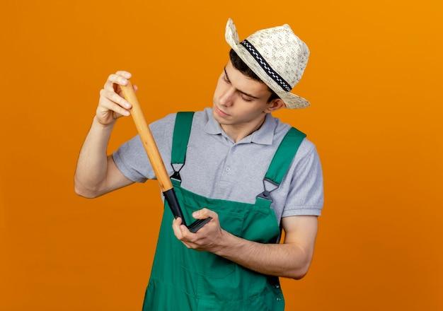 Pewnie młody mężczyzna ogrodnik w kapeluszu ogrodniczym wygląda i trzyma grabie do góry nogami
