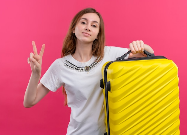 Pewnie młody podróżnik dziewczyna trzyma walizkę robi znak pokoju na odizolowanej różowej przestrzeni