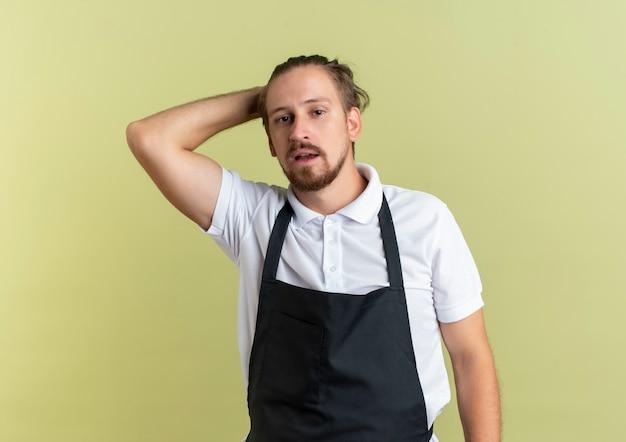 Pewnie młody przystojny fryzjer kładąc rękę na głowie stojąc i patrząc na białym tle na oliwkowej zieleni z miejsca na kopię