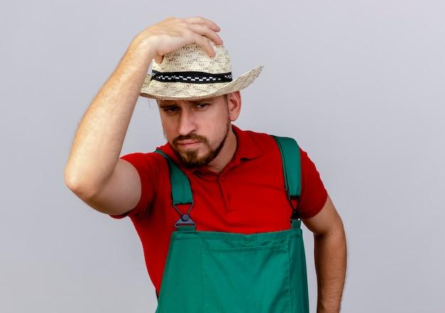 Pewnie młody przystojny ogrodnik słowiański w mundurze i kapeluszu, kładąc rękę na kapelusz i patrząc na białym tle