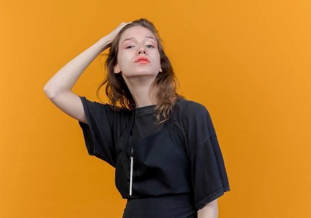 Pewnie młody słowiański fryzjer kobieta ubrana w mundur patrząc na kamery i kładąc rękę na głowie na białym tle na pomarańczowym tle z miejsca na kopię