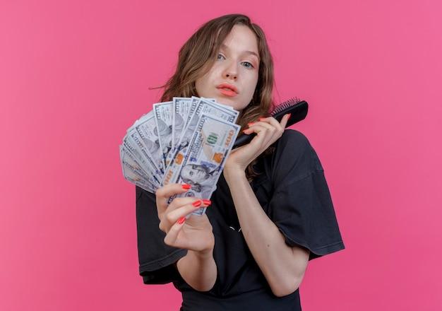 Pewnie młody słowiański fryzjer kobieta ubrana w mundur trzymając grzebień i wyciągając pieniądze w aparacie na białym tle na różowym tle z miejsca na kopię