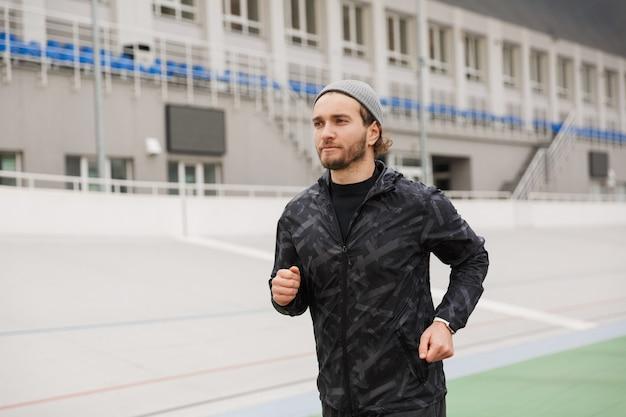 Pewnie młody sprawny sportowiec biegający na torze wyścigowym na stadionie na zewnątrz
