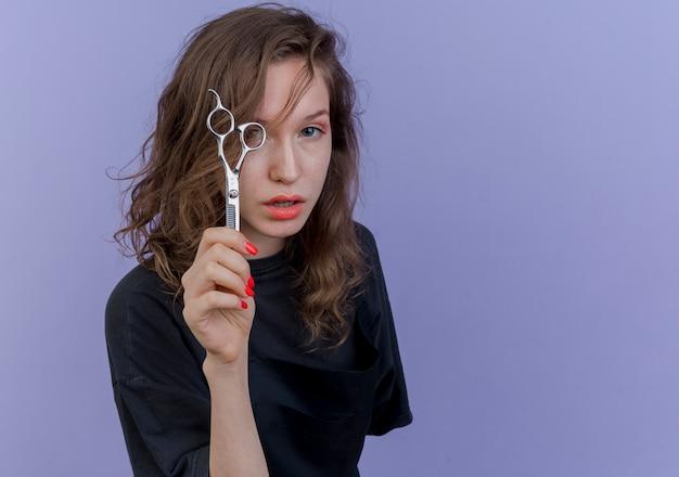 Pewnie młodych kobiet fryzjer na sobie mundur trzymając nożyczki patrząc z przodu