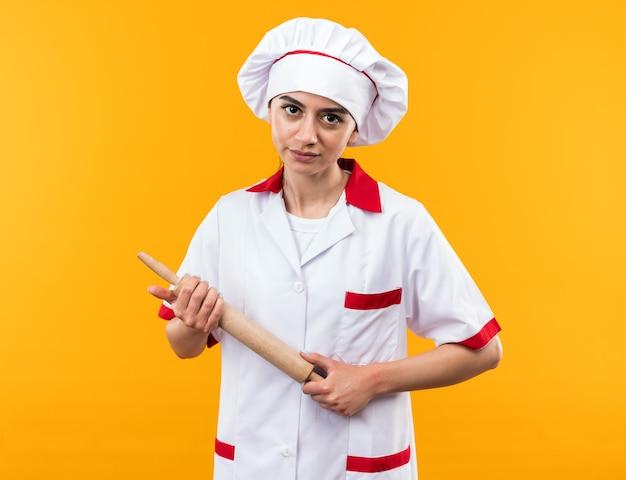 Pewnie patrząc na kamery młoda piękna dziewczyna w mundurze szefa kuchni trzymająca wałek do ciasta