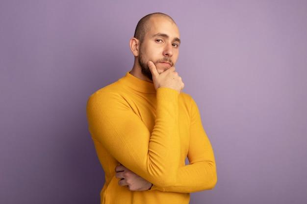 Pewnie patrząc prosto przed siebie młody przystojny facet złapał brodę na białym tle na fioletowo z miejsca na kopię