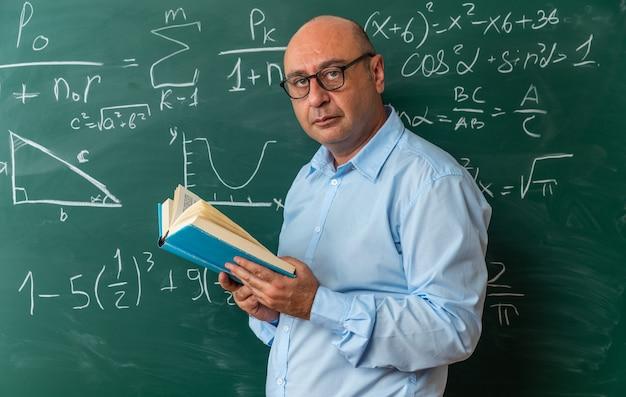 Pewnie patrzący aparat nauczyciel w średnim wieku w okularach stojący przed tablicą trzymającą książkę
