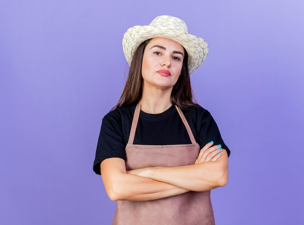 Pewnie piękna dziewczyna ogrodnik w mundurze na sobie kapelusz ogrodniczy skrzyżowaniu rąk na białym tle na niebieskim tle