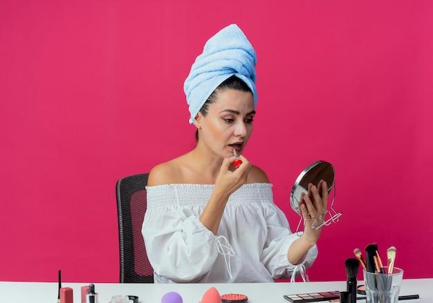 Pewnie piękna dziewczyna owinięty ręcznikiem do włosów siedzi przy stole z narzędziami do makijażu, trzymając i nakładając szminkę, patrząc w lustro na białym tle na różowej ścianie