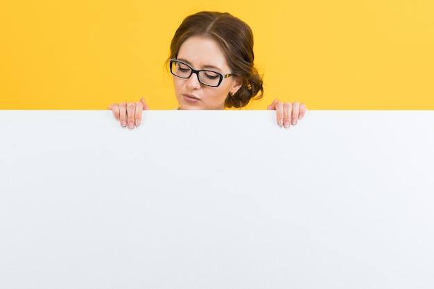 Pewnie piękna szczęśliwa uśmiechnięta młoda biznesowa kobieta pokazuje pustego billboard na kolorze żółtym