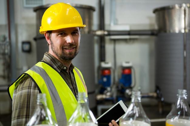 Pewnie pracownik płci męskiej trzymając cyfrowy tablet w fabryce