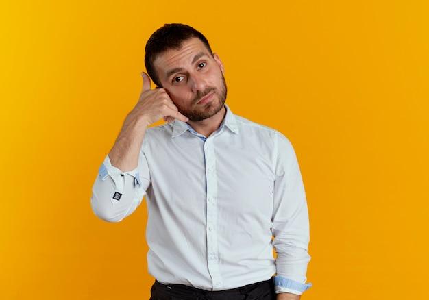 Pewnie przystojny mężczyzna gesty zadzwoń do mnie znak na białym tle na pomarańczowej ścianie