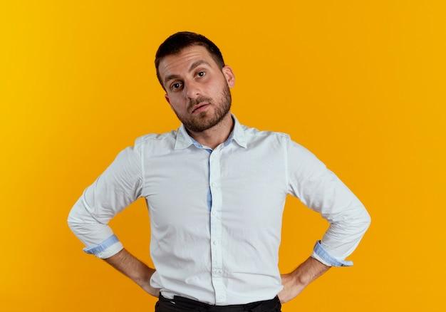 Pewnie przystojny mężczyzna kładzie ręce na talii na białym tle na pomarańczowej ścianie
