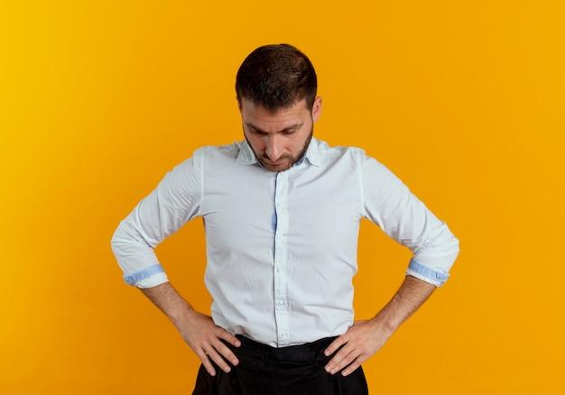 Pewnie przystojny mężczyzna kładzie ręce na talii patrząc w dół na białym tle na pomarańczowej ścianie