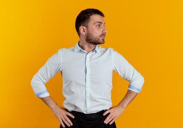 Pewnie przystojny mężczyzna kładzie ręce na talii patrząc z boku na białym tle na pomarańczowej ścianie