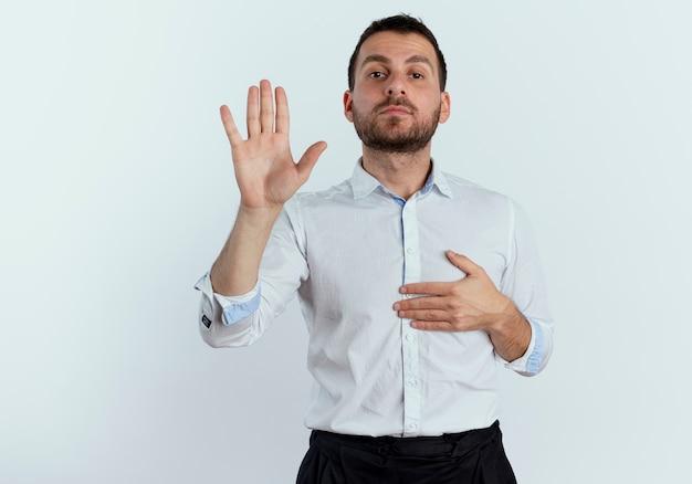 Pewnie przystojny mężczyzna kładzie rękę na klatce piersiowej i podnosi rękę na białym tle na białej ścianie